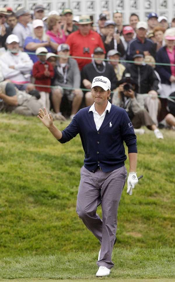Webb Simpson waves after chipping on the 18th