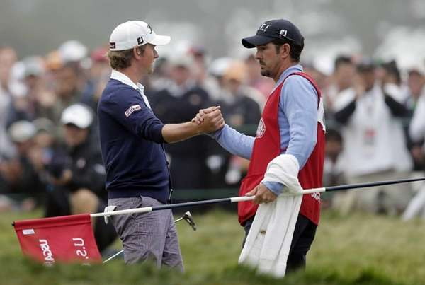 Webb Simpson is congratulated by his caddie Paul