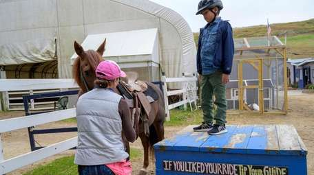 With assistance from an equestrian volunteer, Blake Sabolboro,