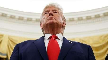 President Donald Trump stands during a Presidential Medal