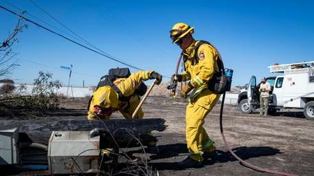 Firefighters with Cal Fire examine a burned down