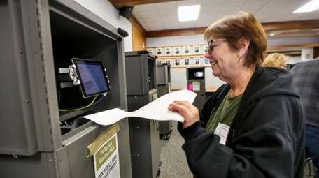 Election worker Lynda Lupoletti grabs a ballot from