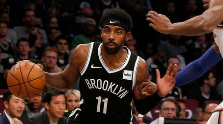 Kyrie Irving of the Nets drives against RJ