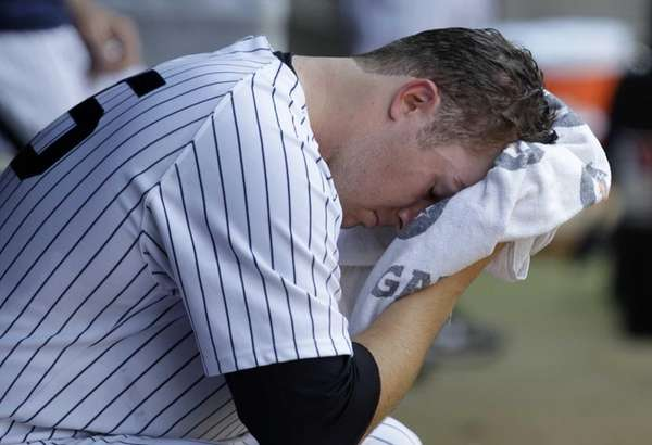 Yankees starting pitcher Phil Hughes wipes his face