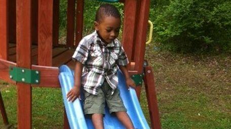 Jonathan slides on his cousin's swing set over