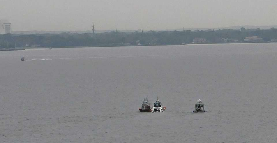 The white boat in middle is towed by