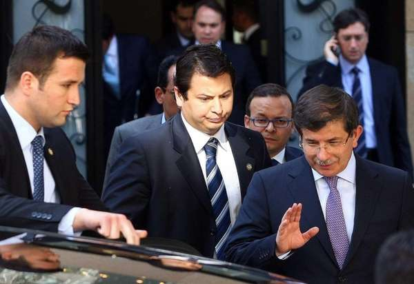 Turkey's Foreign Minister Ahmet Davutoglu (R) leaves a