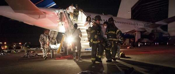 "First responders help carry a ""wounded"" passenger off"