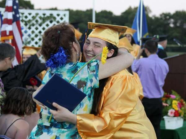 A graduate gets a hug after receiving her