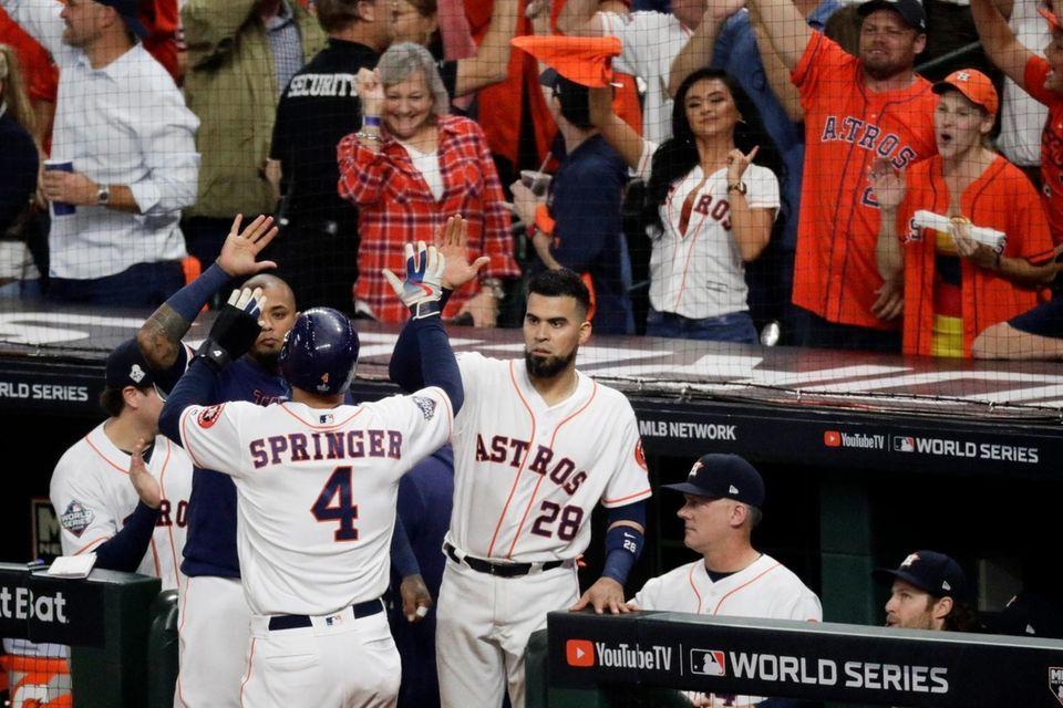 Houston Astros' George Springer celebrates at the dugout