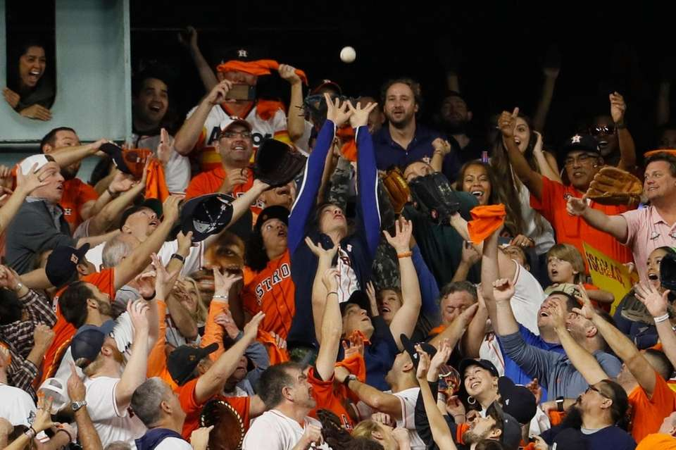 Fans try to catch a Houston Astros' Alex