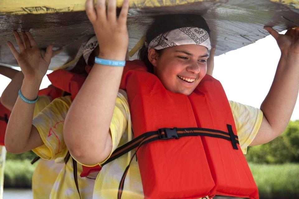 Stefanie Costello, 15, of Calverton helps carry her