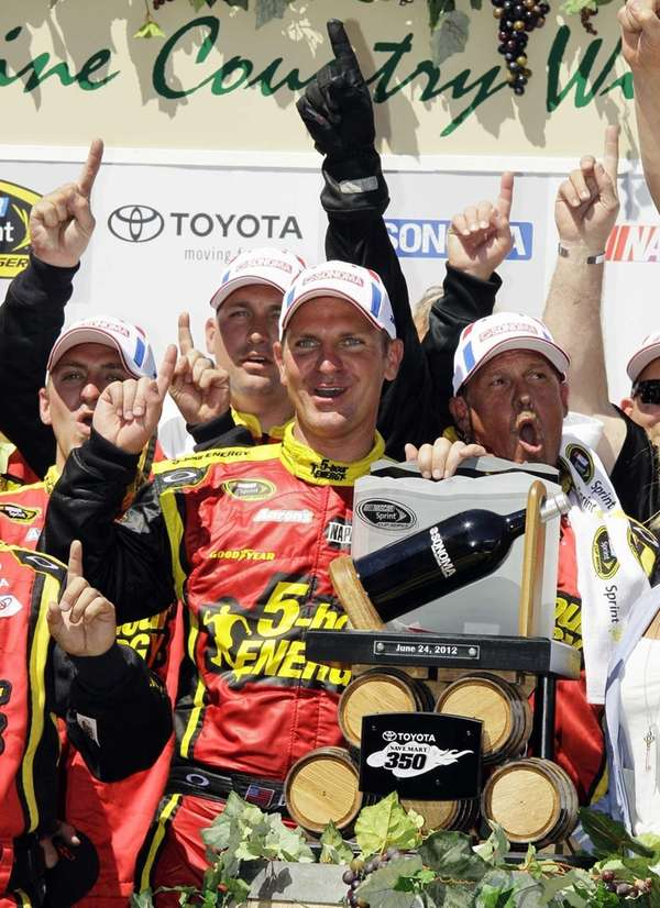 Clint Bowyer poses by his trophy after winning