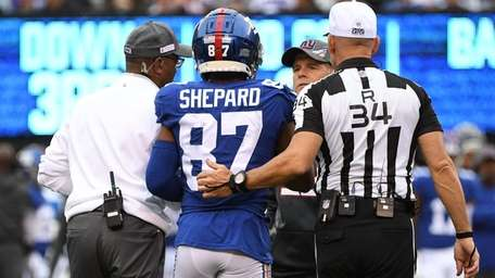 Sterling Shepard is escorted off the field after
