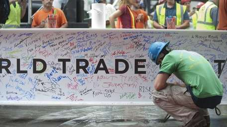 Construction workers sign the final steel beam before
