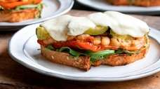 An open-faced dinner sandwich with roasted vegetables, lightly