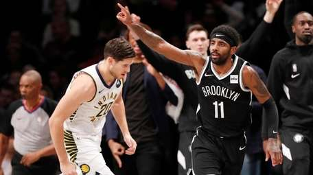 Nets guard Kyrie Irving gestures as he runs