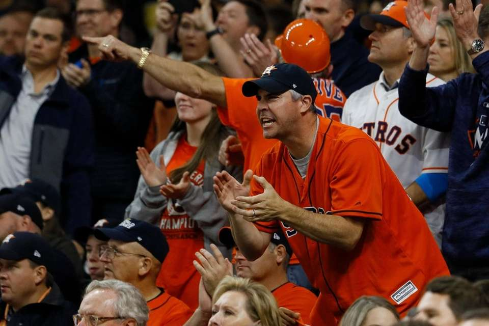 Fans cheer during the seventh inning of Game