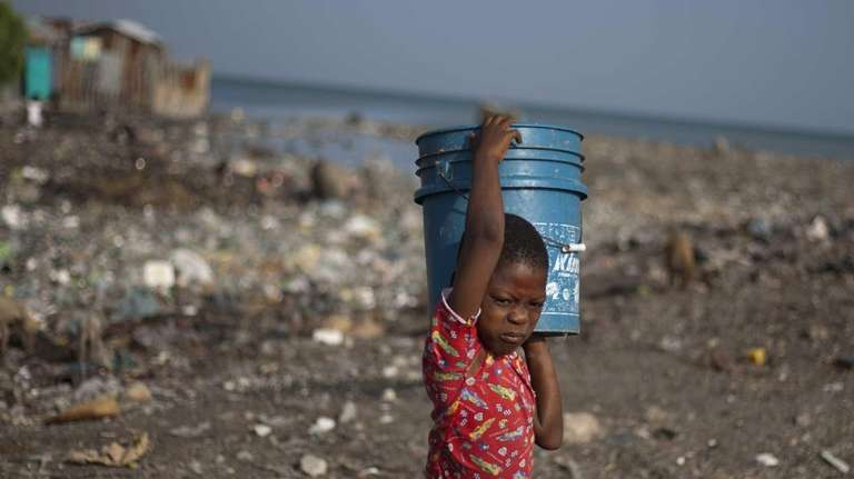 A boy carries home a bucket of water