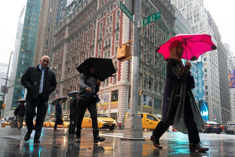 People walk in Times Square during a rain