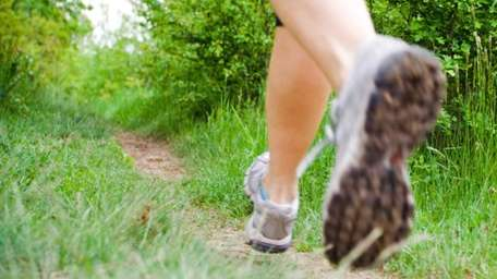 Woman running in forest, cross country fitness, motion