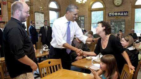 President Barack Obama visits patrons before eating an