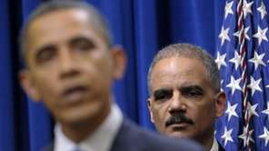 Attorney General Eric holder listens at right as
