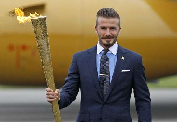David Beckham holding the Olympic torch during the