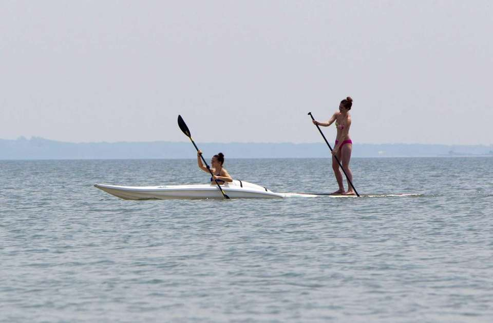 A kayaker and stand up paddler glide across