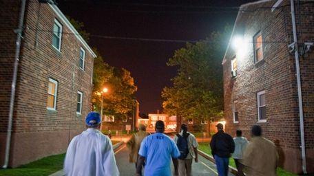 Activists march through a Hempstead Village neighborhood plagued