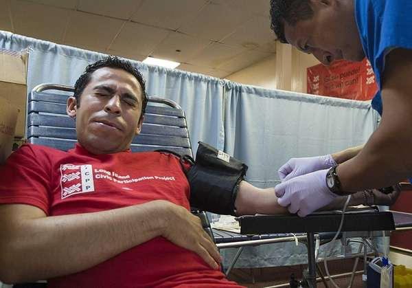 Donor specialist Oscar Clara right taking blood from