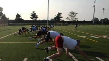 Boot campers bear crawl across the football field
