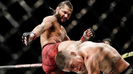 Jorge Masvidal, left, kicks Nate Diaz during the