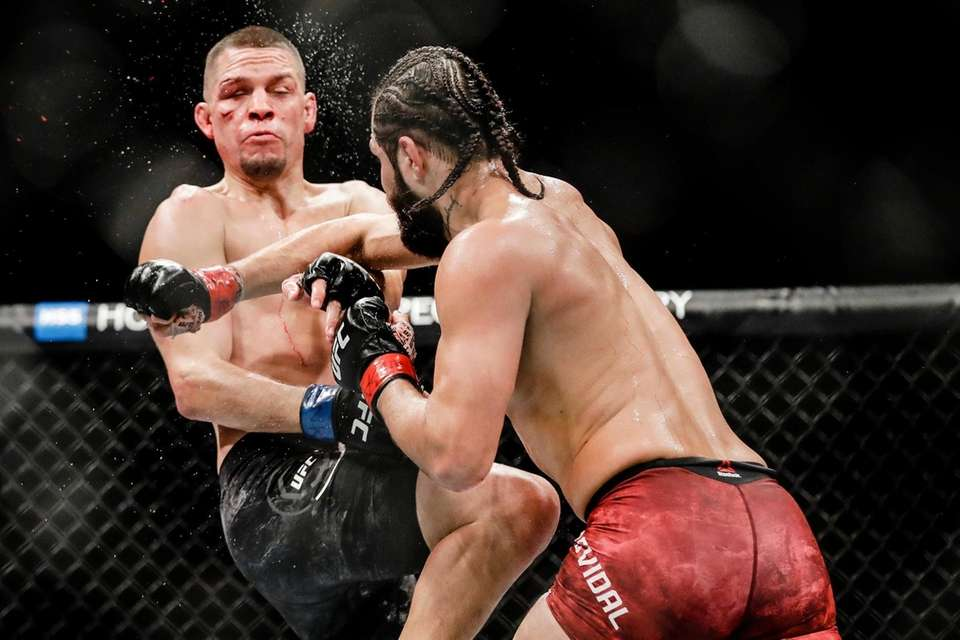 Jorge Masvidal, right, punches Nate Diaz during the