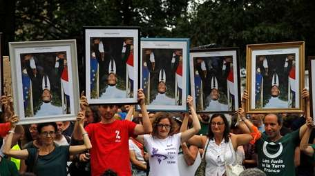 Demonstrators hold up upside down portraits of French