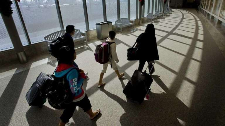 Travelers, with luggage in hand, make their way