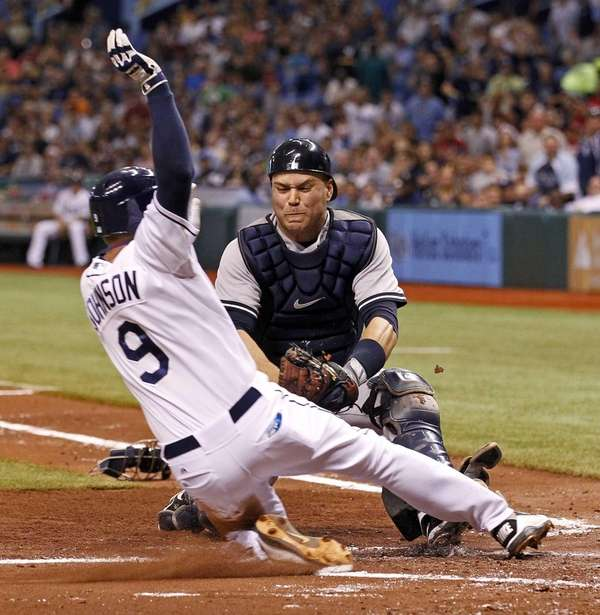 Tampa Bay's Elliot Johnson slides into Yankees catcher