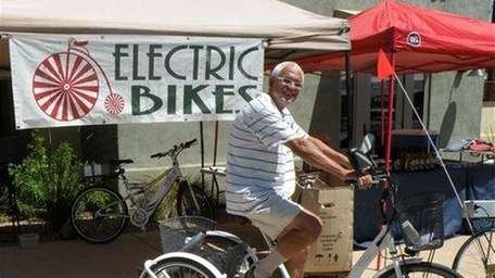 Fermin Cruz demonstrates one of the electric bikes