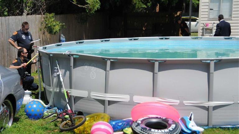 Investigators check the measurements of a pool at