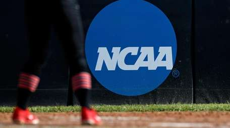 An athlete stands near a NCAA logo during