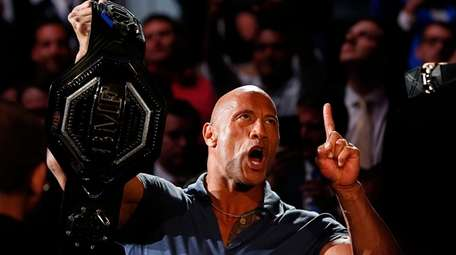 "Dwayne ""The Rock"" Johnson holds the belt prior"