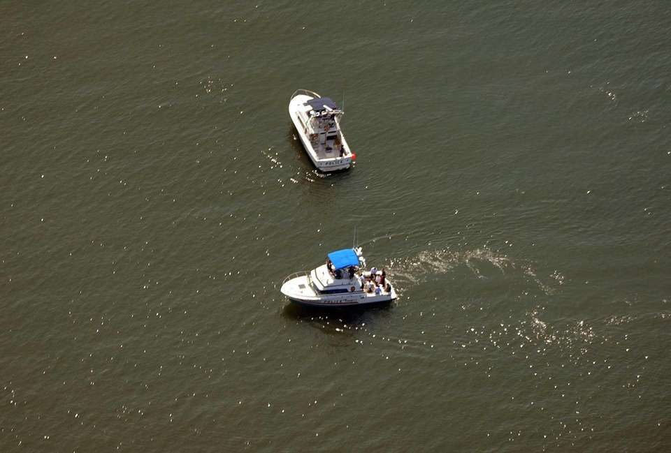 An aerial view of police boats searching for