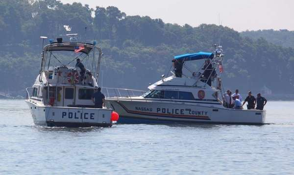 Police boats search for a capsized vessel about 1/4 mile west of Lloyd Neck in Cold Spring Harbor. Police say three children died after the cabin cruiser, returning from a fireworks display, capsized. (July 5, 2012)