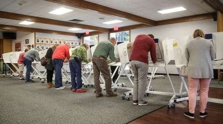 Voters fill out their ballots on the first