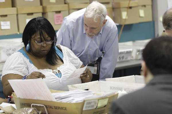 Board of elections officials LaCheryl Karmadozie, left, and