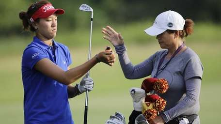 Annie Park takes a club from her caddie