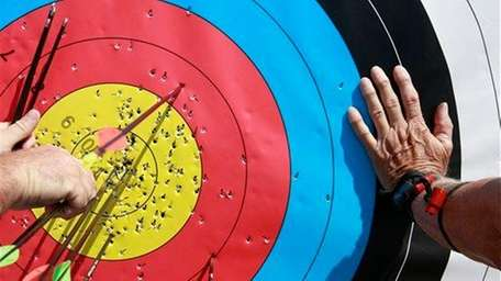 Men try to pull arrows from a target