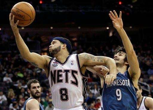 Deron Williams, left, takes a shot as he