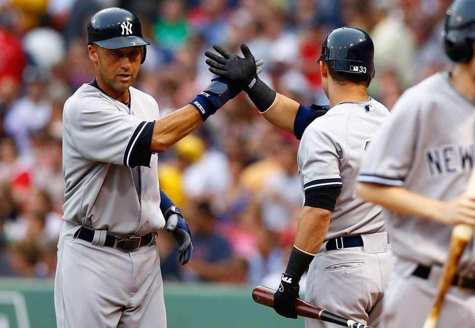 Derek Jeter is congratulated by teammate Nick Swisher