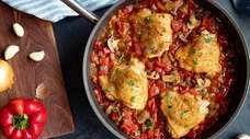 Chicken thighs are simmered with red bell peppers,